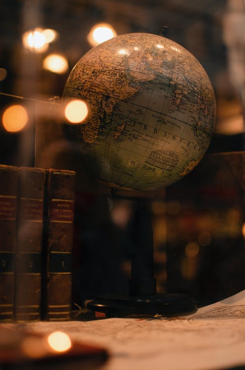 Through glass of world globe and ancient books placed behind transparent display in museum