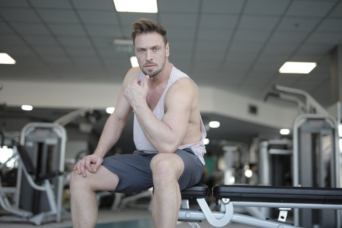 Focused young sportsman resting on bench after workout in fitness club