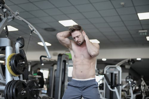 Muscular sportsman with naked torso warming up  neck muscles with hands during workout in gym