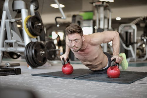 Serious muscular sportsman doing push ups on kettlebells in modern gym