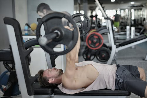 Strong sportsman doing bench press during workout in modern gym