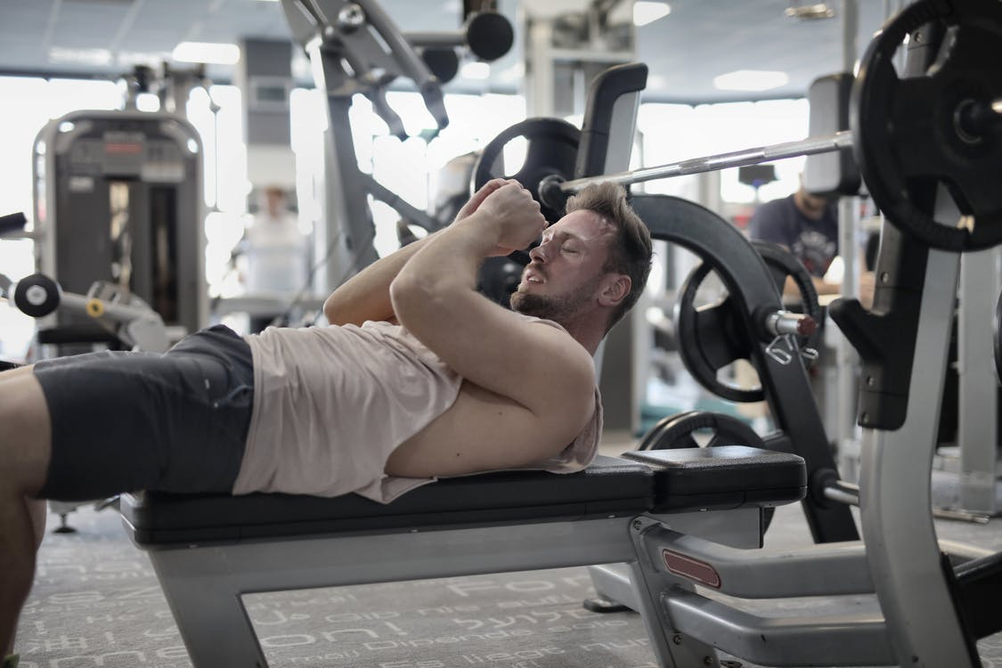Focused muscular sportsman in modern sportswear preparing to workout with heavy barbell on bench training in modern gym