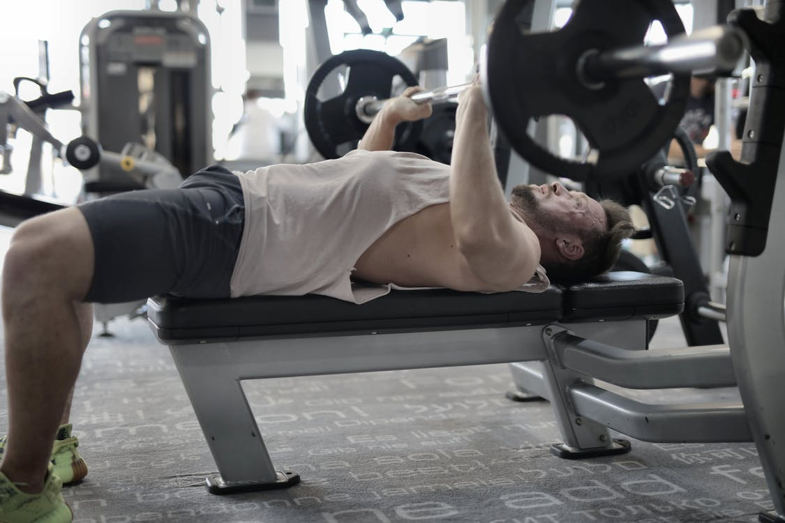 Strong sportsman working out on bench in modern gym