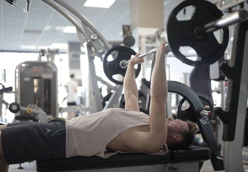 在現代健身房舉重鍛煉期間與重的槓鈴肌肉運動員訓練