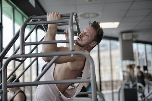 Side view of strong muscular male athlete in casual sportswear doing chin ups during intense training in modern fitness center