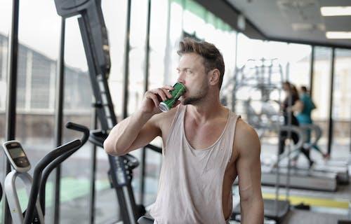 疲倦的年輕男運動員在健身房鍛煉後休息時喝能量飲料