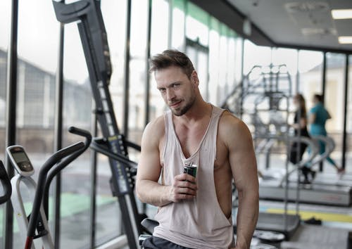 Positive young muscular bearded male athlete in casual sportswear standing near window in modern gym with bottle of cold energy drink and looking at camera