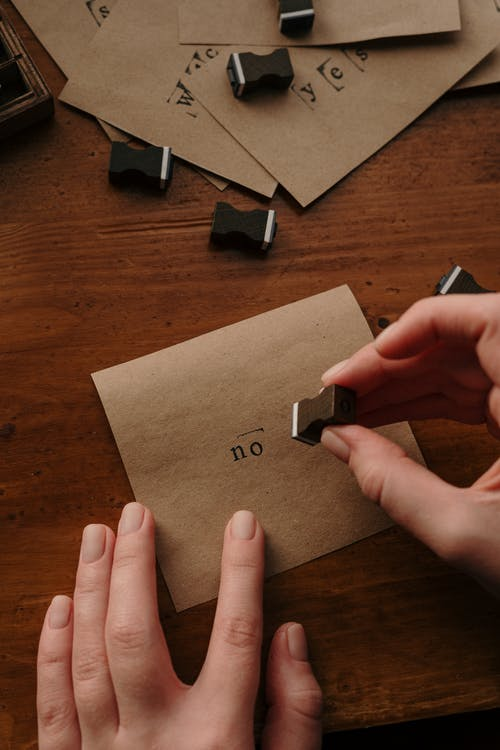 Person Holding Brown Paper With Black and White Usb Cable