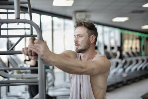 Serious young male athlete resting after workout in modern fitness club