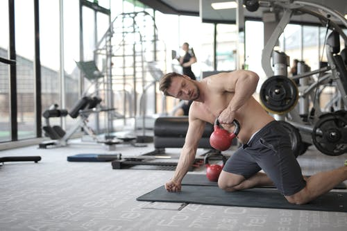 Topless Man Kneeling on Black Mat Lifting Dumbbell