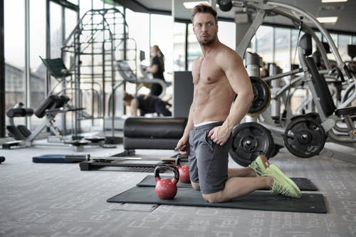 Serious muscular sportsman with naked torso doing exercise with kettlebells in gym