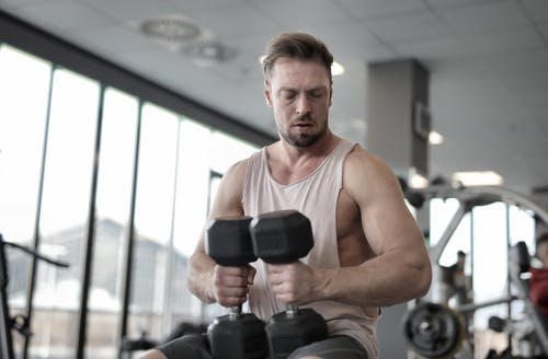 Man In Tank Top Holding Dumbbells