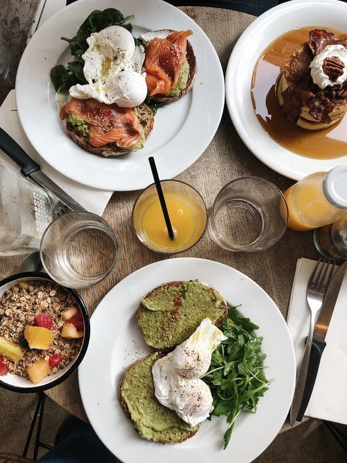Top view of plates of assorted healthy toasts with poached eggs and natural juice served on wooden table near oatmeal bowl and sweet pancakes