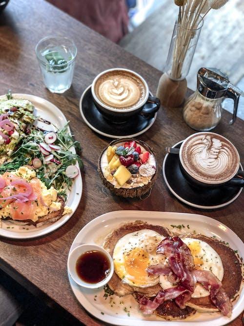 Platos Apetitosos Y Tazón De Batido Colocado Sobre La Mesa Con Tazas De Café En La Cafetería Moderna