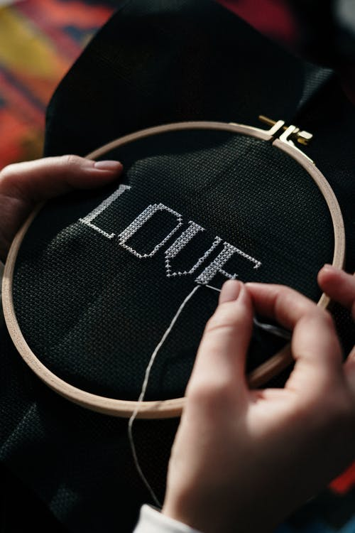 Person Hand Embroidering on Black Textile