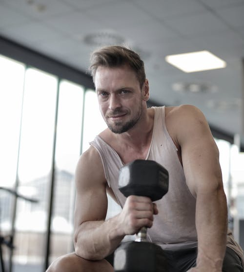 Man In Tank Top Holding A Dumbbell