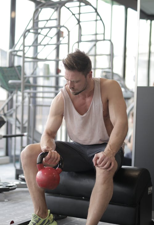 Man In White Tank Top Lifting Kettlebell