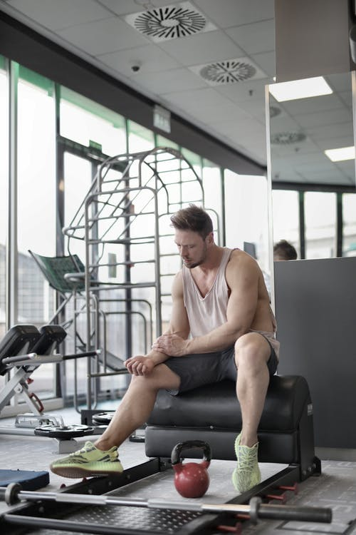 Tired young muscular male athlete sitting on bench with kettlebell and barbell and looking on arm while resting after workout in modern fitness center