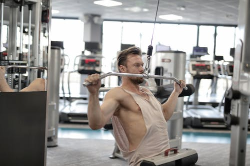 Powerful muscular male athlete in casual sportswear performing exercise with metal bar on machine while training hard in modern fitness club