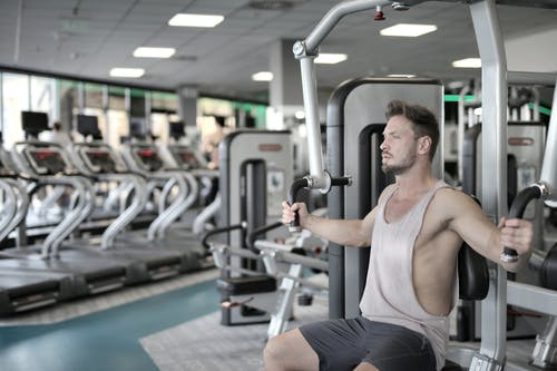 Man in White Tank Top and Grey Shorts Sitting on Exercise Equipment