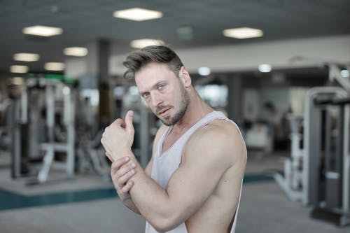 Serious male athlete standing in gym and looking at camera