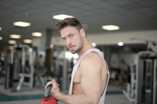 Strong confident sportsman holding kettlebell in hand while training in gym and looking at camera