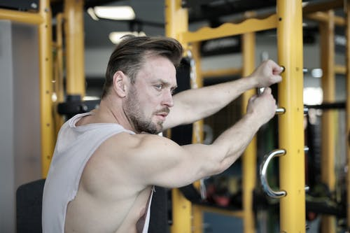 Serious muscular male athlete training near exercise machine in fitness center