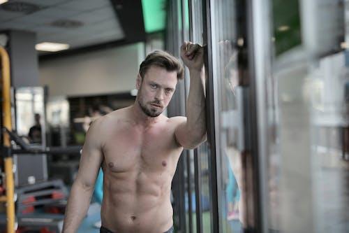 Shirtless Man Leaning On Glass Window