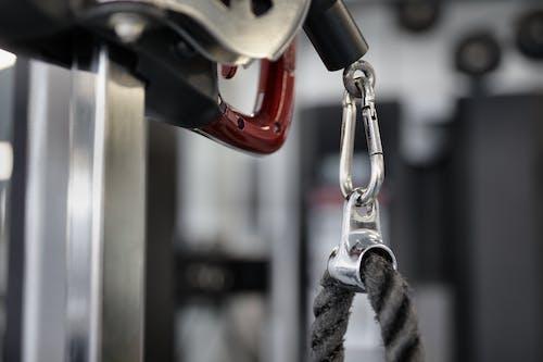 Black rope of modern exercise machine hanging on metal carabiner