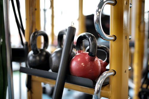 Set of different kettlebells placed in row on metal platform on modern fitness equipment in sport center