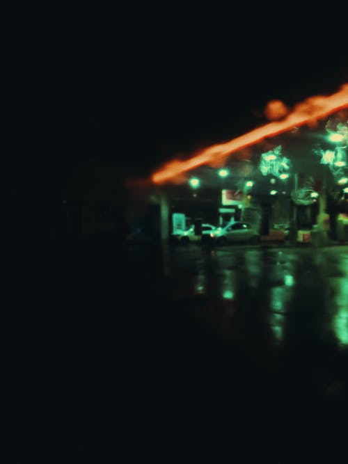 Defocused cars on gas station with neon illumination at night in rainy weather