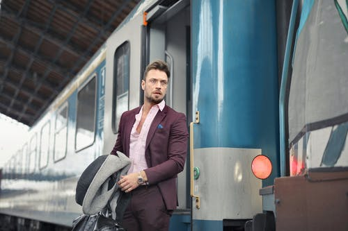 Serious bearded male passenger in stylish suit standing near train with travel bag and coat in hand and looking away