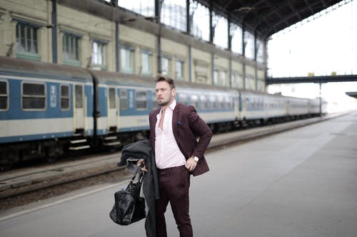 Serious stylish businessman in elegant white shirt and purple jacket holding leather bag and coat in hand standing on platform on railway station and waiting for train