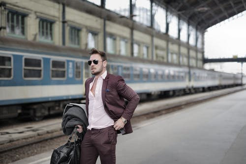 Confident trendy male traveler in sunglasses standing on platform on railway station