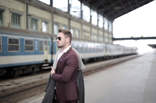 Confident stylish passenger standing on railway station and waiting for departure