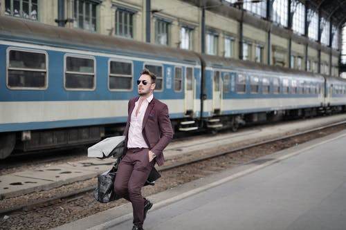 Man in Pink Dress Shirt and Brown Suit Carrying Luggage Walking Beside Train