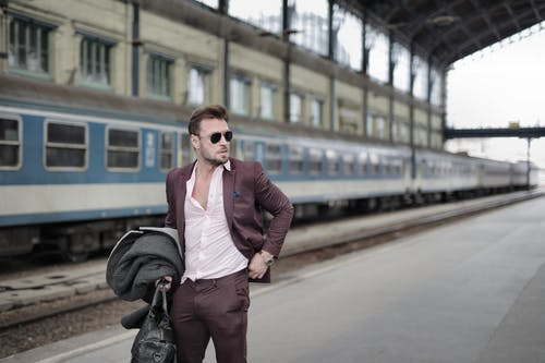 Confident trendy male traveler standing on railroad platform with coat and travel bag