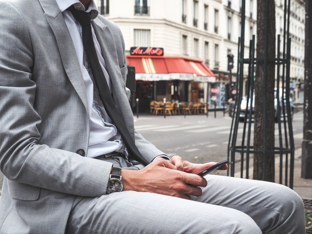 Man in Gray Suit Jacket and Gray Dress Pants Sitting on Bench