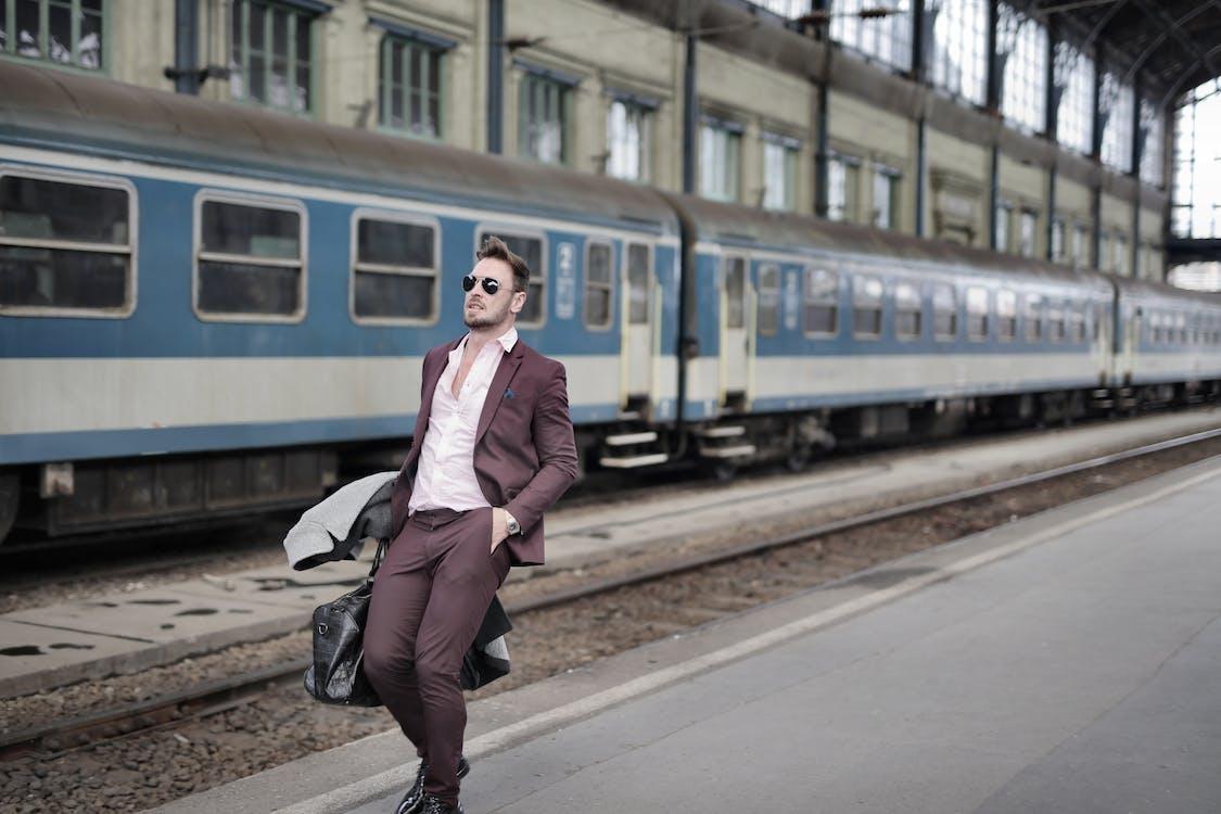 Man in Maroon Suit Walking on Sidewalk Beside Train
