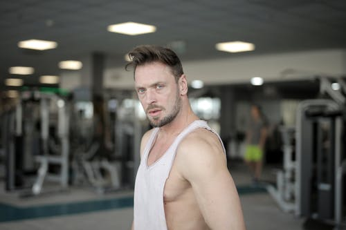 Serious young bearded male athlete in casual sportswear standing in modern fitness center while resting after workout and looking at camera