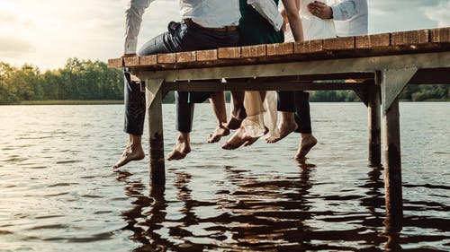 People Sitting on Brown Wooden Dock
