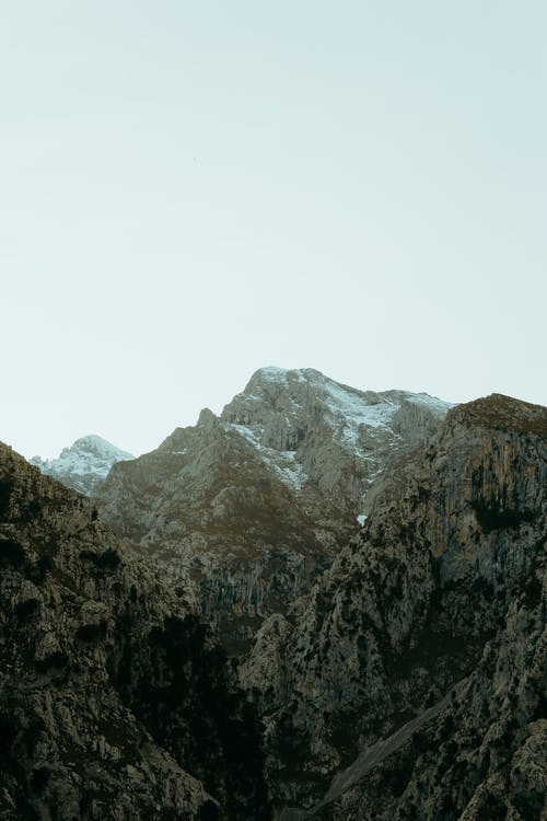 Mountain ridge with snowy peaks under cloudless sky