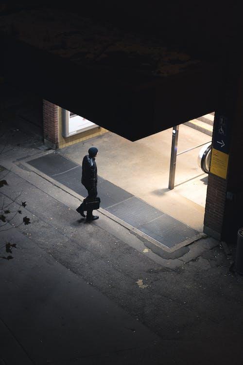 Unrecognizable person walking on street towards building entrance