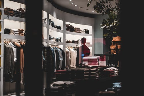 Back view of faceless elegant male customer in suit choosing new clothes while standing near wardrobe in modern fashion boutique