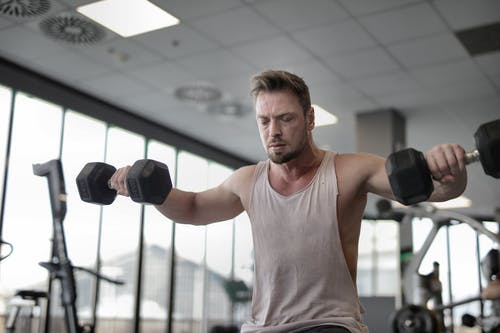 Man in Gray Tank Top Holding Black Dumbbells