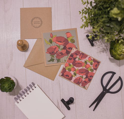 Set of handmade invitation cards and stationery placed on table near houseplants