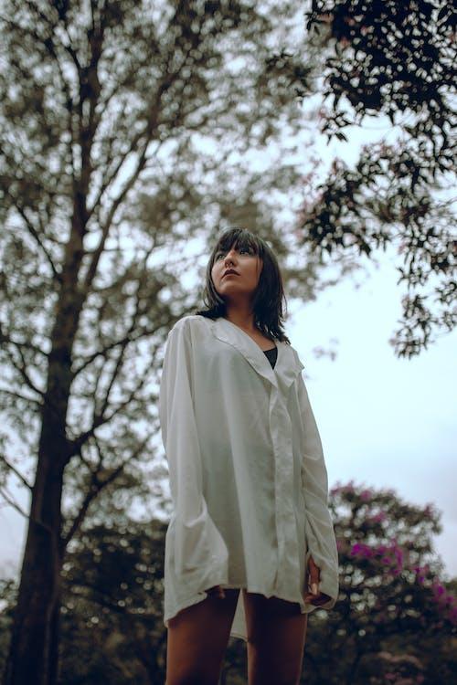 Donna In Camicia Bianca A Maniche Lunghe In Piedi Sotto L'albero Verde