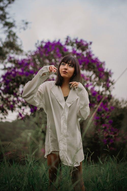 Woman in White Coat Standing Near Purple Flower