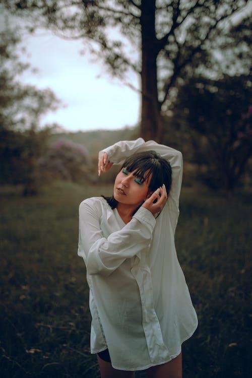 Donna In Vestito Bianco A Maniche Lunghe Che Copre Il Viso Con La Mano
