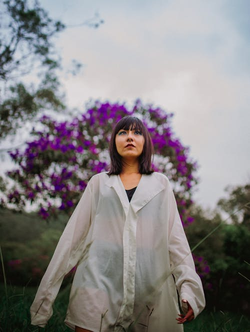 Woman in White Coat Standing Near Purple Flower Field